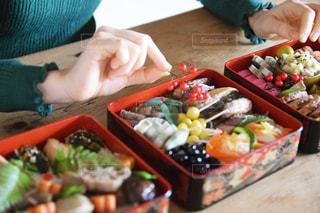 アンティークなテーブルの上でおせち料理を詰める女性の写真・画像素材[2912949]