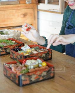 おせち料理を楽しそうに詰めている女子の写真・画像素材[2912953]