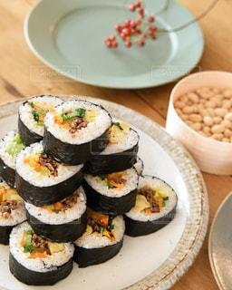 皿の上に食べ物の皿をトッピングした木製のテーブルの上の寿司の写真・画像素材[2930096]