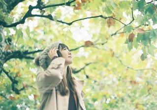 木の隣に立っている女性 - No.1056