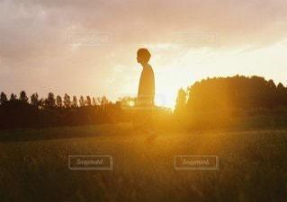 バック グラウンドで夕日を持つ男の写真・画像素材[1069]