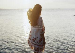 水の体の横に立っている人の写真・画像素材[1076]