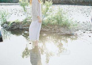 川の横に立っている人の写真・画像素材[1228]