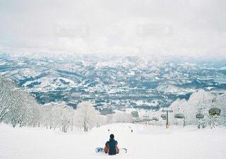 煙る山頂の雪をスノーボードに乗る男の写真・画像素材[1351]