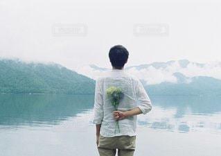 水の体の横に立っている人の写真・画像素材[1394]