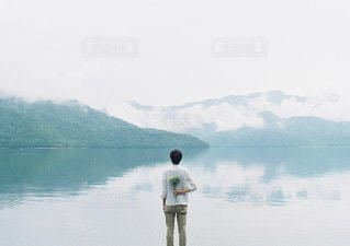 水の体の横に立っている人 - No.1385