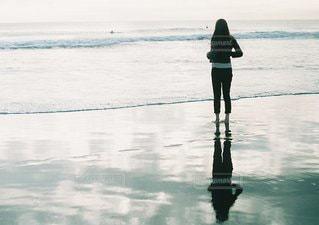 水の体の横に立っている人の写真・画像素材[1357]