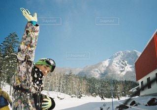山が、雪の上に空気を通って飛んで男に覆われています。 - No.1171