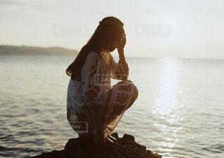 水の体の横に立っている人の像の写真・画像素材[1090]
