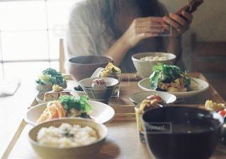 テーブルの上にボウルに食糧を準備する女性の写真・画像素材[1300]