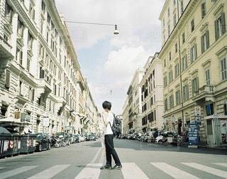 街の通りの真ん中に立っている男の写真・画像素材[101]