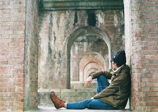 れんが造りの建物の前にあるベンチに座っている男の写真・画像素材[1356]