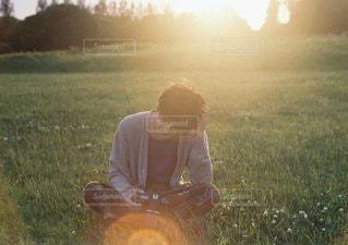 草の上に座っている男にフィールドが覆われています。の写真・画像素材[1053]