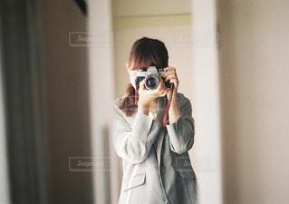 カメラにポーズ鏡の前に立っている女性の写真・画像素材[915328]