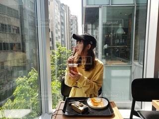 食卓に座って食べ物を食べる女性の写真・画像素材[2103146]