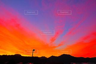背景にオレンジ色の夕日の写真・画像素材[2392777]