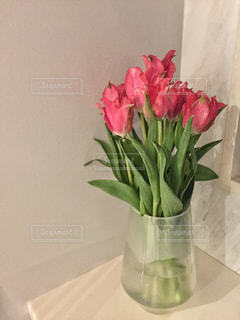 テーブルの上に座っての花で一杯の花瓶の写真・画像素材[1014619]