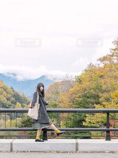 フェンスの前に立っている人の写真・画像素材[1612014]