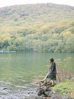 水の体の横に立っている人の写真・画像素材[1612017]