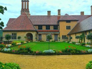 大規模なれんが造りの家の前に緑の芝生と建物 - No.743102