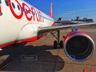 赤と白の飛行機の駐機場に座っての写真・画像素材[802432]