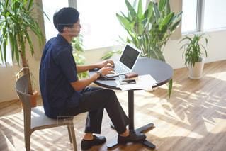 ラップトップ コンピューターを使用してテーブルに座っている人の写真・画像素材[706279]