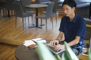 ラップトップ コンピューターを使用してテーブルに座っている少年の写真・画像素材[706283]