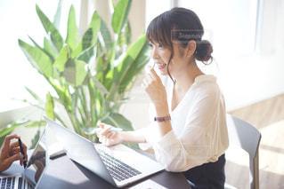ラップトップ コンピューターを使用してテーブルに座っている女性の写真・画像素材[799603]