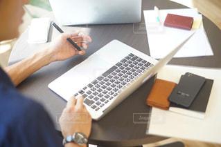 ラップトップ コンピューターを使用してテーブルに座っている男の人 - No.799606