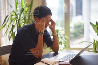 ラップトップ コンピューターを使用してテーブルに座っている男の人の写真・画像素材[880622]