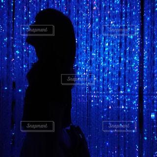 光のカーテンの前に立っている人の写真・画像素材[1461657]