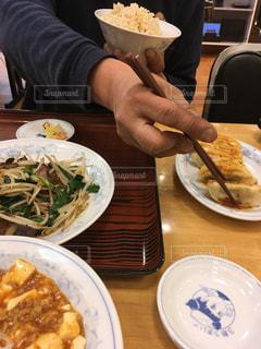 片手に玄米ご飯持ちつつ餃子食べようとする男性の写真・画像素材[3089741]