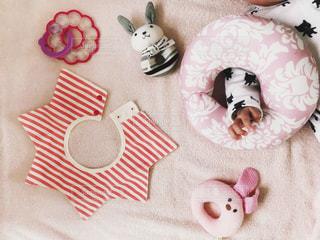 赤ちゃんとまくらとおもちゃとよだれかけ。の写真・画像素材[1127264]