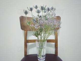 椅子とグラスに生けた花の写真・画像素材[1246833]