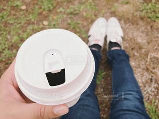 紙カップのコーヒーを持った手の写真・画像素材[1718696]
