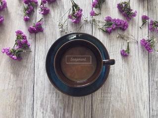 木製テーブルの上の紫の花とコーヒーの写真・画像素材[1758114]