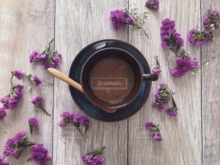 木製テーブルの上の紫の花とコーヒーの写真・画像素材[1758115]