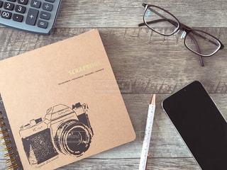 ノートとスマホとペンと眼鏡と電卓の写真・画像素材[1803036]