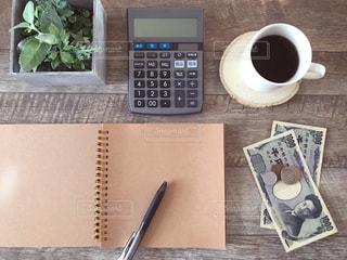 ノートと電卓とお金とコーヒーの写真・画像素材[1803038]