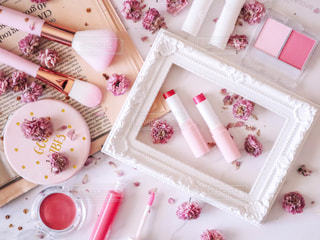 ピンクのコスメたちと八重桜のドライフラワーの写真・画像素材[2110295]