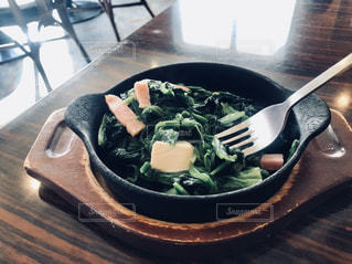 木製のテーブルの上に座っている食べ物のボウルの写真・画像素材[2798183]