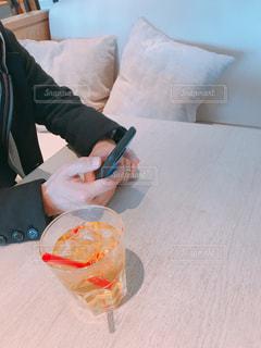 食事のテーブルに座ってスマホを触る男性の写真・画像素材[1651432]