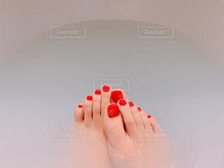 乳白色の湯船と赤いペディキュアの写真・画像素材[1832906]