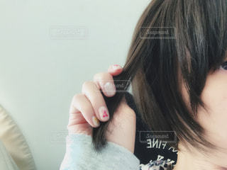 黒っぽく髪色を戻してジェルネイルもした女性の写真・画像素材[2069063]