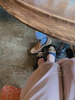 テーブルの下のカップルの靴の写真・画像素材[2118563]