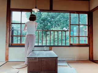 レトロ古民家の窓の前に立っている女性の写真・画像素材[2377786]