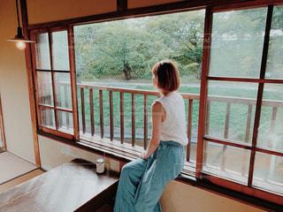 レトロ古民家の窓の前に座っている人の写真・画像素材[2377795]