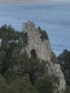 岩が多い丘の上に立っている人の写真・画像素材[766166]