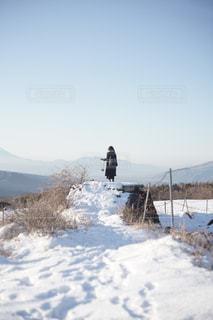 雪に覆われた丘の上に立っている女の人の写真・画像素材[2765640]