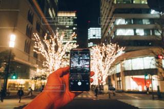 携帯電話を持って通りを歩いている人 - No.749522